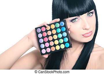rouge - Beautiful young woman holding eye shadow palette....