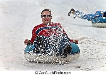 Man Tubing in Snow - A man on a tube being sprayed by the...