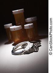 Handcuffs, Medicine Bottle and Pills Under Spot Light