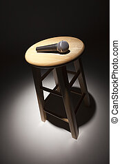 Microphone Laying on Wooden Stool Under Spotlight Abstract