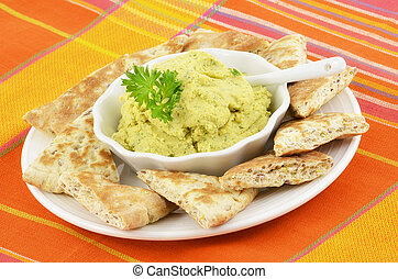 Hummus - Fresh homemade hummus with pita bread triangles on...