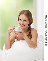 beautiful girl drinking coffee in bed