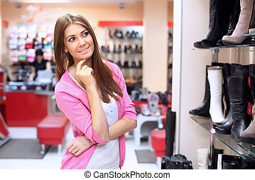 Shopping in clothes store - Young woman doing shopping in...