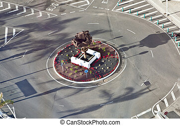 roundabout with sculpture of old cars