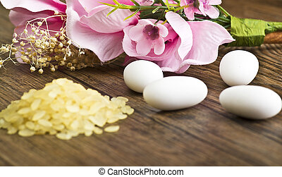 rice, confetti and flowers close up on wood table