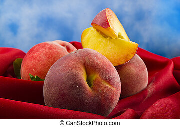 fresh peach fruits with cut on red velvet