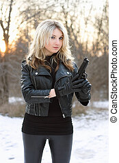Curious pretty woman holding a gun in winter forest