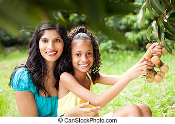 mother and daughter picking litchis - pretty young mother...