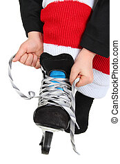 Tying skates - Young boy tying his Ice Skates in hockey...
