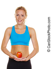 a young woman in sports clothing holding an apple in his hand
