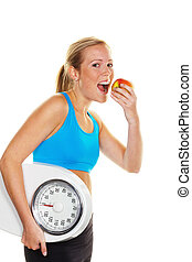 young woman with bathroom scale and apple. successful diet