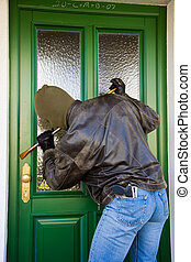 burglars at a house door - a burglar breaking in the door of...