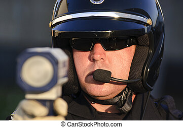 radar gun - a police officer pointing his radar gun at...