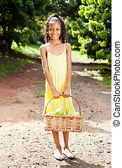 happy little girl with basket of apples outdoors in orchard