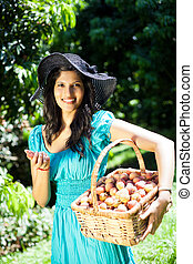 woman picking litchis in orchard - young attractive woman...