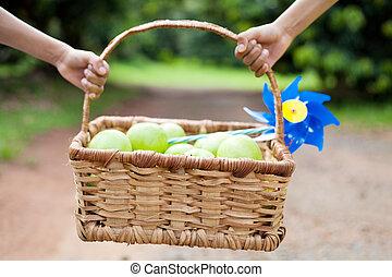kids carrying fruit basket outdoors