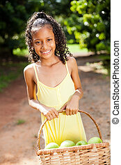 happy little girl with basket of apple in orchard