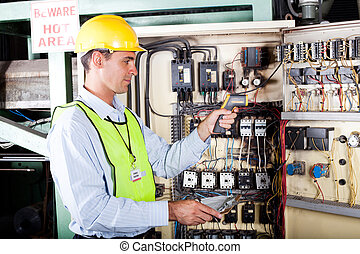 electrician checking industrial machine - male caucasian...