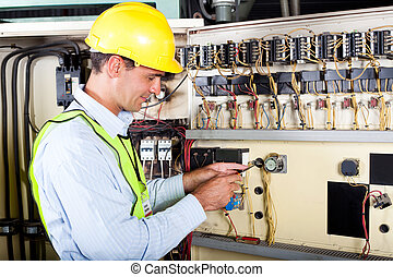 electrician changing industrial machine switch