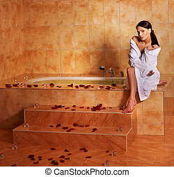 Woman relaxing in bath. - Woman sitting on edge of bath tub.