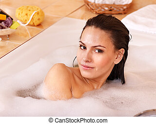 Woman relaxing in bath.