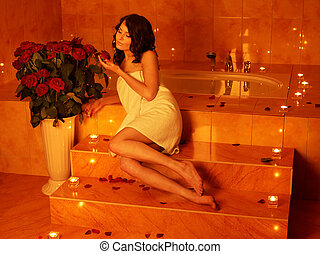 Woman relaxing in bath. - Woman sitting on edge of sauna.