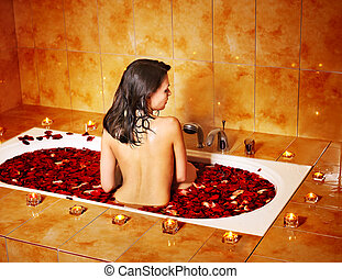 Woman relaxing in bath. - Woman relaxing in bath with rose...