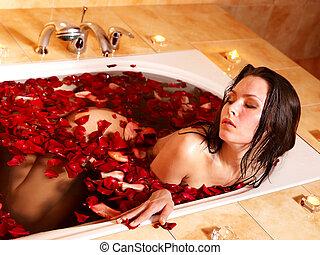 Woman relaxing in bath. - Woman relaxing in bath with rose...