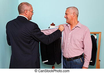 Man being measured for a bespoke suit - Photo of a tailor...
