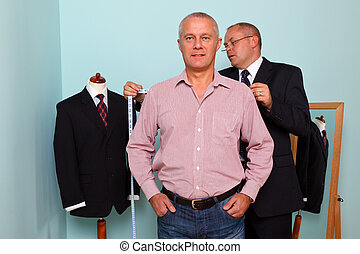 Man being fitted for a bespoke suit - Photo of a tailor...