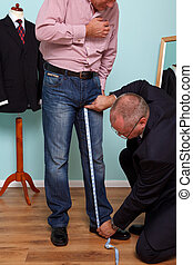 Man having inside leg measured by a tailor for a bespoke...