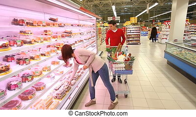 Taking products - Young woman taking products from the...