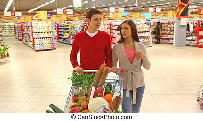 At shopping mall - Cheerful couple walking through mall with...