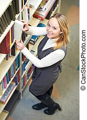 young adult student choosing book in library