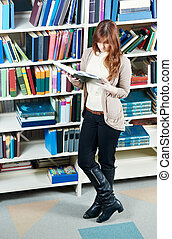 young student girl reading book in library