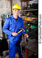 happy blue collar worker working in workshop