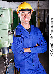 portrait of industrial machinist standing next to machine...