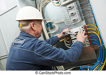Electrician tighten the screws with spanner - One...
