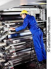 operator checking machine - modern printing machine operator...