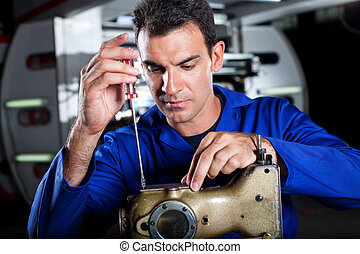 skilled mechanic repairing industrial sewing machine in...