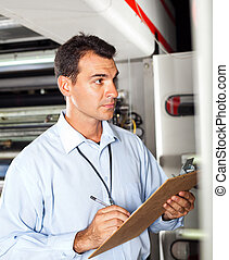 industrial technician taking machine readings