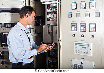 technician writing down machine data - technician writing...
