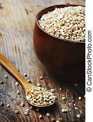 Buckwheat in bowl on wooden background