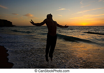 silhouette of a man jumping at the beach