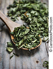 Green tea - Spoon of dried green tea leaves on wooden...