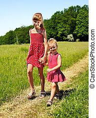Kids walking across green grass outdoor.