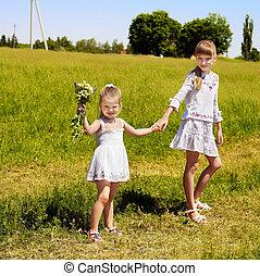 Kids running across green grass outdoor.