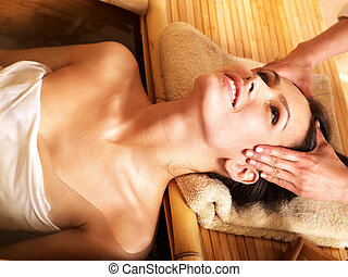 Woman getting massage in bamboo spa. - Young woman getting...