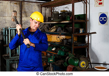factory blue collar worker using big hammer in workshop