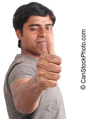 Portrait of happy young indian giving thumbs up over white...